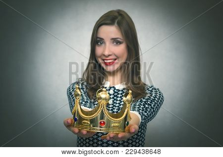 Happy Woman Is Stretching Ahead A Gold Crown Isolated On Gray Background. Award Ceremony. Transfer O