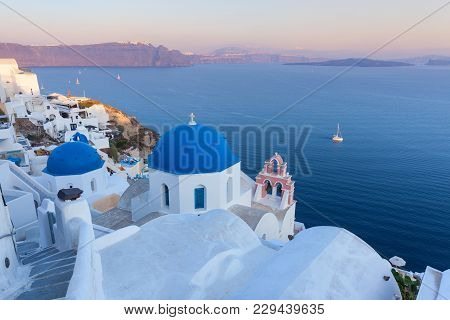 Famous Three Blue Domes In Village Oia At Beautiful Sunset, Santorini Island Greece.