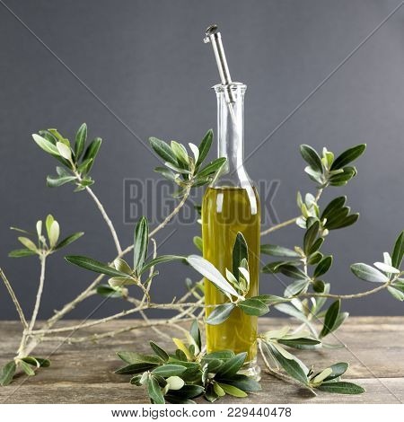 The Bottle On The Wooden Table Contains Extra Virgin Olive Oil Produced In Italy.
