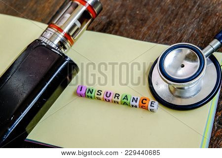 Insurance Word Block Concept With Rusty Cigarret And Stethoscope On Yellow Paper Over Wooden Backgro
