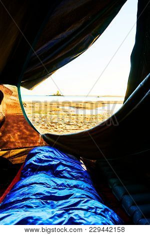 Waking Up During Sunrise. View Out Of A Tent At The Beach Looking At The Sand And The Water In Swede