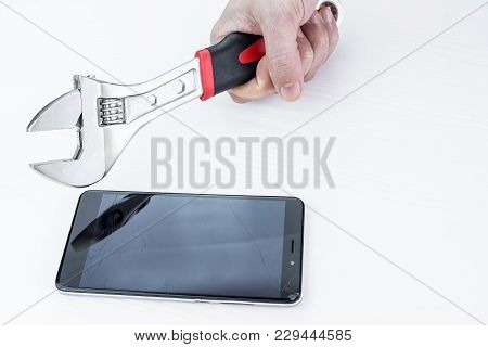 Man Smashes Phone With A Wrench On A White Background