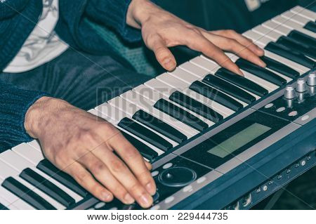 Hands of a pianist. Plays on the synthesizer. Selective focus poster
