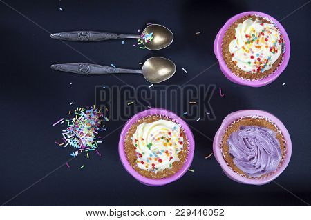 The Cupcakes With White And Violet Cream With Spoons On The Black Background