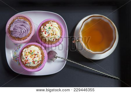 The Cupcakes With White And Violet Cream With Tea And Spoons On The Black Background, Arranged For A