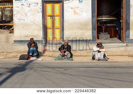 Kathmandu, Nepal - November 13, 2016: Three Men Sit On The Road At The Swayambhunath Temple In Kathm
