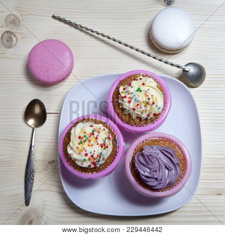 The Cupcakes With White And Violet Cream With Spoons On The Wooden Background, Arranged For A Party