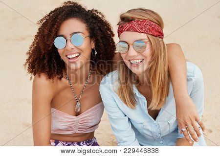 Cheerful Young Females Embrace At Beach, Look Positively Into Distance, Have Fun Together During Sum