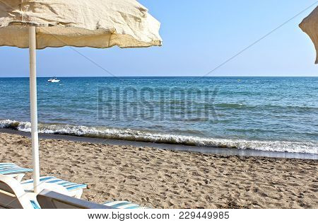 Summertime At The Beach. Beach Umbrellas And Beach Lounge Chairs. Summer Holiday And Vacation Concep