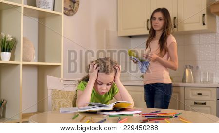 Mom Washing Dishes Watching As Daughter Doing Her Homework With Difficulty, Stock Footage