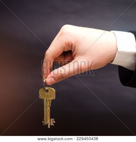 Keys In Hands On A Black Background, Concept Of Selling Real Estate, Buying New Apartment Concepts