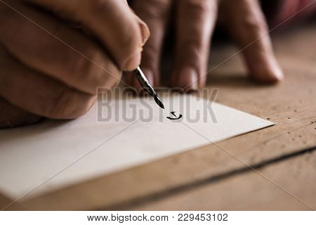 Person Using A Nib Pen And Ink To Do Calligraphy In A Close Up View Of His Hands And The First Lette