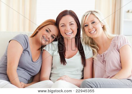 Laughing Friends Sitting On A Sofa