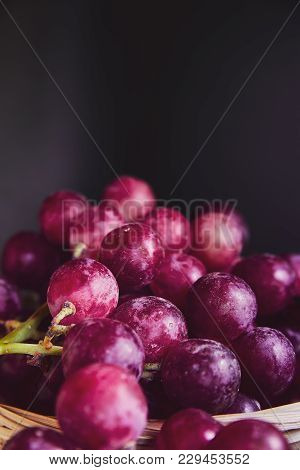 Bunches Of Purple And Red Grapes In A Wicker Basket On A Dark Background. The Harvest Of Unwashed Gr