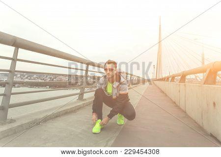 Male Jogger Tying Shoelace On A Big Bridge.