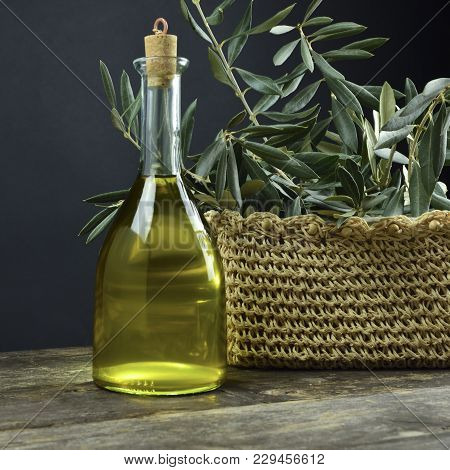 The Bottle On The Wooden Table Contains Extra Virgin Olive Oil Produced In Italy. Chili, Garlic And