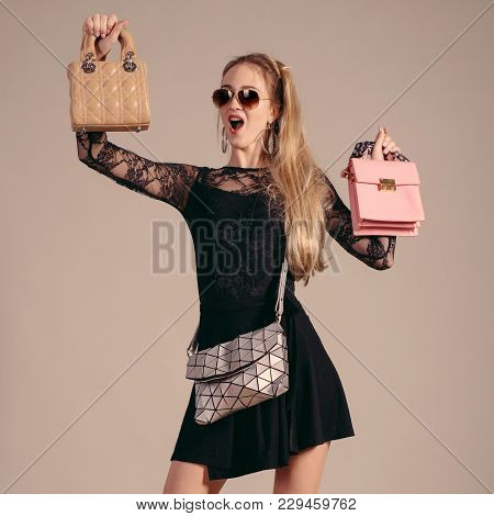 Young Woman Posing In Black Dress And Sunglasses With Three Hand Bag.