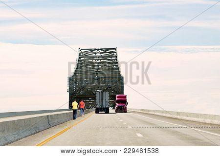 Two Caucasian Weman Walking Along The Side Of The Freeway Under A Tall Concrete Bridge With Semi Tru