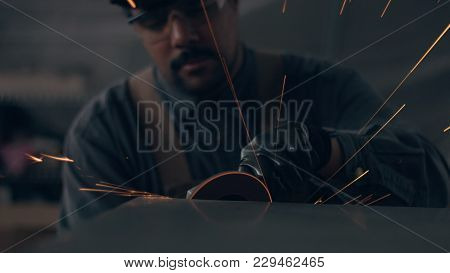 Worker Using Industrial Grinder. Worker In Garage Makes Work With Metall And Grinder. Flying Sparks