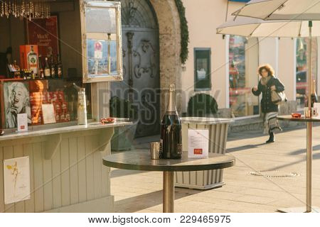 Austria, Salzburg, January 1, 2017: The Usual Street Cafe. Traditionally On The Tables There Are Bot
