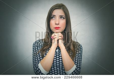 Pensive Wistful Woman Is Wondering And Thinking Isolated On Gray Background. Looking For Solution Or
