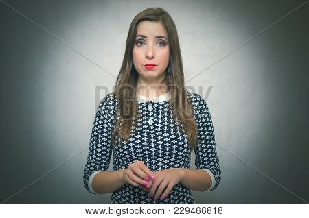 Pensive Modest Woman. Guilty Girl Is Ashamed Isolated On Gray Background.