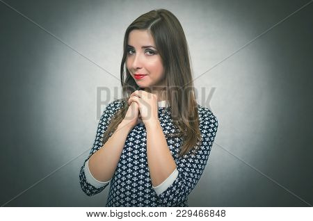 Happy Modest Woman Portrait. Shy Girl Is Smiling Isolated On Gray Background.
