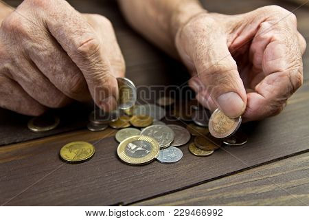 An Elderly Person Holds Coins .hands Of Beggar With Few Coins. The Concept Of Poverty In Retirement.
