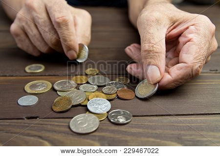 An Elderly Person Holds Coins .hands Of Beggar With Few Coins. The Concept Of Poverty