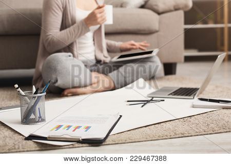 Unrecognizable Woman Drinking Coffee While Working On Laptop And With Documents At Home, Sitting On