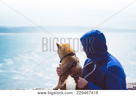 Man With Small Golden Japanese Shiba Inu Dog Sitting Togetherness On A Mountain And Looking At Blue