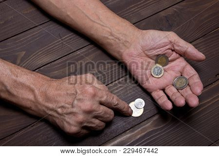 An Elderly Person Holds The Coins .hands Of Beggar With Few Coins. The Concept Of Poverty In Retirem