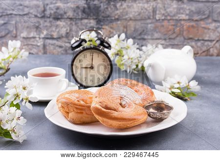 Powdered Choux Pastry With Tea. Table Decorated With Apple Blossom. Alarm Clock As Time For Breakfas