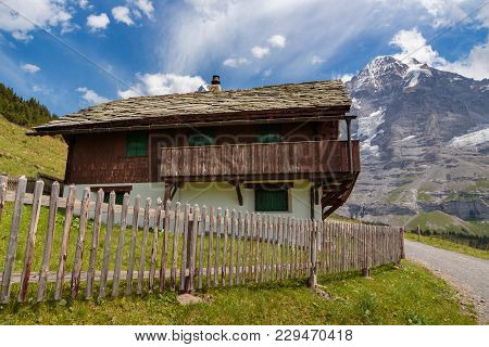 Old Traditional House In The Bernese Alps, Mountain Monch In The Background In Summer. Lauterbrunnen