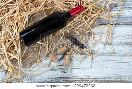 Overhead View Of A Red Wine Bottle Plus Corkscrew With Straw And Burlap On White Rustic Boards