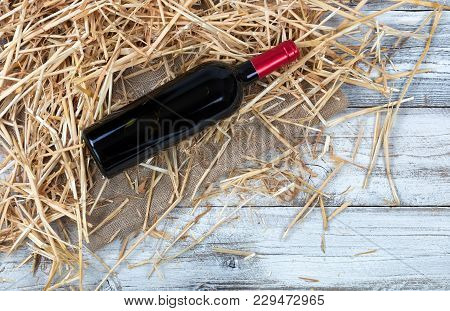 Overhead View Of A Red Wine Bottle With Straw And Burlap On White Rustic Boards