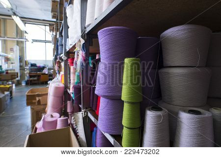 Spools With Different Color Thread Kept On Shelves At Knitting Factory Shot
