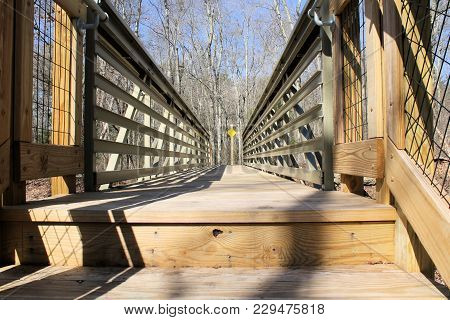 Well Constructed Footbridge Made Of Non Rusting Girders And Pressure Treated Wood.