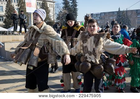 Pernik, Bulgaria - January 26, 2018: Boys In Traditional Fur Costumes And Several Big Brass Ritual B