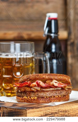 Sandwich With Beef, Fried Onion, Cheese And Bacon With Granular Mustard. Beer And Snack On The Table