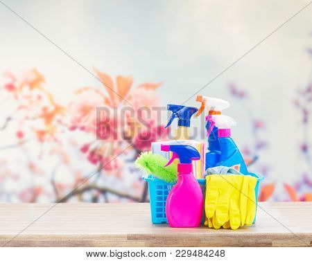 Spring Cleaning Concept - Colorful Sprays Bottles And Rubbers On Wood Table Over Spring Background