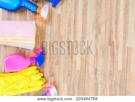 Spring Cleaning Concept - Colorful Sprays Botles And Rubbers On Woode With Copy Space