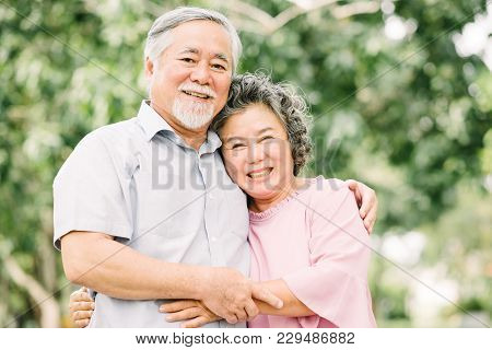 Happy Asian Senior Couple Having A Good Time And Smiling While Holding Each Other Outdoor In The Par
