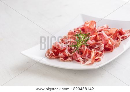 Prosciutto. Curled Slices Of Delicious Italian Prosciutto With R