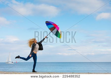 Happiness, Enjoying Cold Autumn Weather, Feeling Great Concept. Woman Jumping With Colorful Umbrella