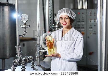 Line Of Food Production Of Refined Sunflower Oil. Girl Worker At A Factory On A Conveyor Background