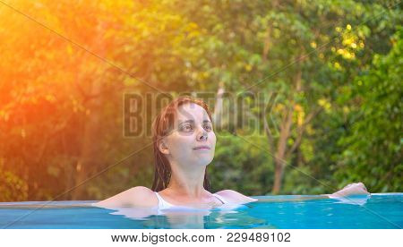 Relaxed Woman In Blue Swimming Pool. Girl In Open Swimming Pool. Tropical Jungle Resort. Summer Vaca