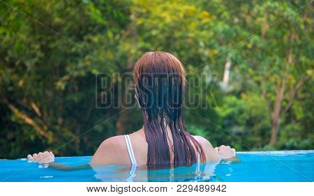 Woman In Blue Water. Loose Hair Girl In Open Swimming Pool. Tropical Jungle Resort. Summer Vacation