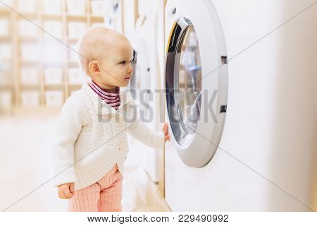 Little Baby Girl Looking At A Washing Machine