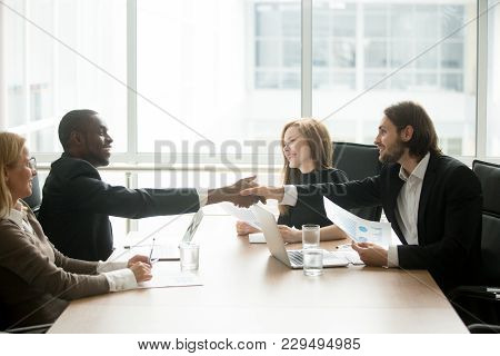 Satisfied Multiracial Businessmen In Suits Shaking Hands At Executive Team Office Meeting, Two Diver